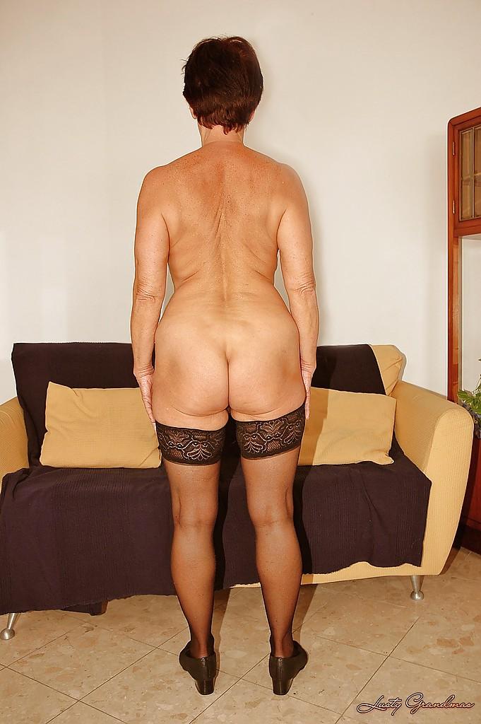 Короткостриженная старушка  раздевается на фоне дивана секс фото и порно фото