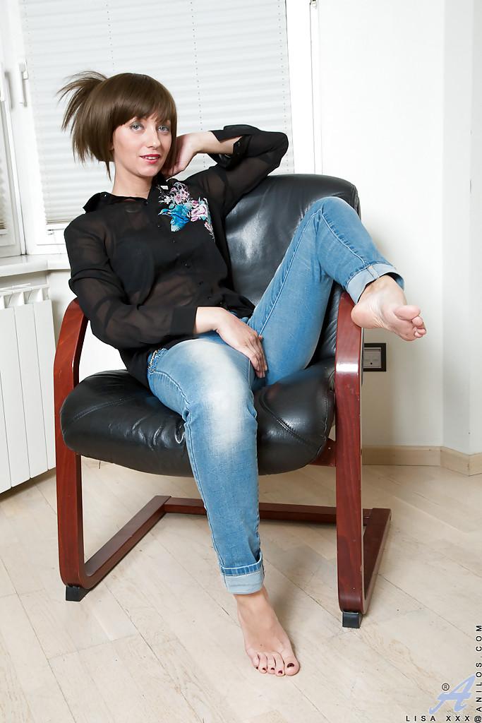 Плоская девушка широко расставляет ноги, сидя на кожаном кресле секс фото и порно фото