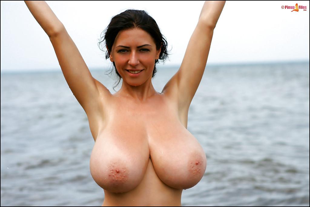 Брюнетка оголяет огромные дойки на берегу моря секс фото и порно фото